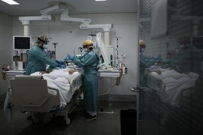 Dos enfermeros atienden a un paciente con covid-19 en la UCI del hospital Sant Pau de Barcelona