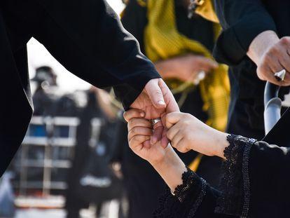 Un niño agarra con fuerza la mano de su padre.