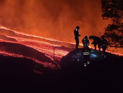 Cinco miembros de la Unidad Militar de Emergencias recogen muestras de lava en el volcán de La Palma.