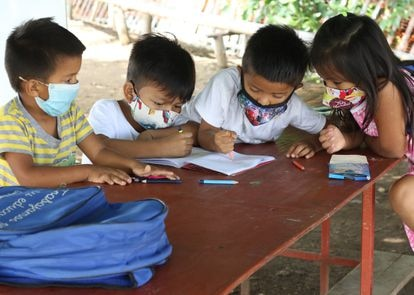Cuatro alumnos hacen sus deberes al aire libre en una de las clases que se imparten de manera informal en Monte Sinaí, uno de los barrios más pobres de Guayaquil. Pulse en la imagen para ver la fotogalería completa.