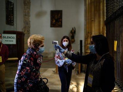 Una mujer toma la temperatura a otra en las puertas de la catedral de Alcalá de Henares el 3 de mayo