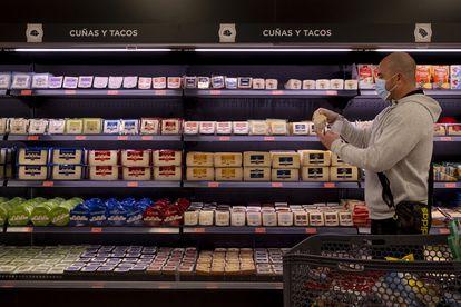 Un vecino de Sevilla hace la compra en una de las tiendas de Mercadona donde está implantado ya el laboratorio de quesos nacionales.