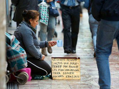 Una mujer pide en una calle de Valencia.