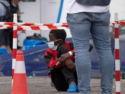 Un niño aguarda sentado en el puerto de Los Cristianos de Tenerife tras ser rescatado por Salvamento Marítimo este lunes.