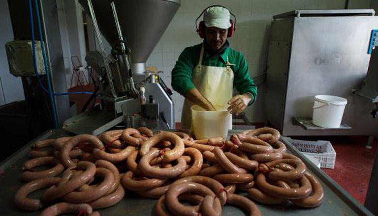Un trabajador elabora chorizos en una fábrica de Extremadura.