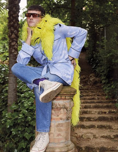 Palomo wears the Blue Brocade Safari Jacket from its Palomo Spain brand;  Curro glasses, by Palomó;  pants from Levi's and sneakers from Converse.