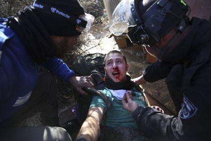 Policías israelíes trasladan a la fuerza a un colono judío durante la evacuación del asentamiento de Amoná en Cisjordania (Palestina).