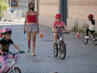 Varios niños junto a la monitora, el pasado martes durante una clase para aprender a montar en bici en Matadero Madrid.