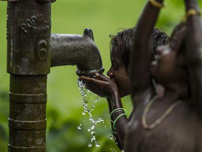 Unos niños beben agua de un pozo en Madhubani, en la región india de Bihar.