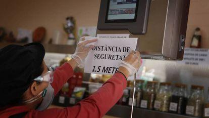El encargado de un negocio de alimentación en Terrassa (Cataluña) coloca un cartel de advertencia en el mostrador.