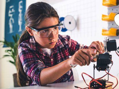 Una niña construye un robot.