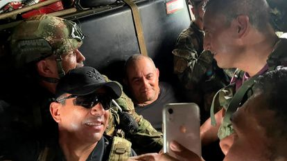 """Dairo Antonio Usuga David, alias """"Otoniel"""", top leader of the Gulf clan, poses for a photo while  escorted by Colombian military soldiers inside a helicopter after being captured, in Turbo, Colombia October 23, 2021. Colombian Defense Ministry/Handout via REUTERS ATTENTION EDITORS - THIS IMAGE HAS BEEN SUPPLIED BY A THIRD PARTY. MANDATORY CREDIT. NO RESALES. NO ARCHIVES."""