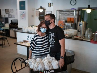 Paloma de Diego y Jaime Rincón se dan un abrazo en Casa Carmela, restaurante que reparte menús solidarios de comidas.