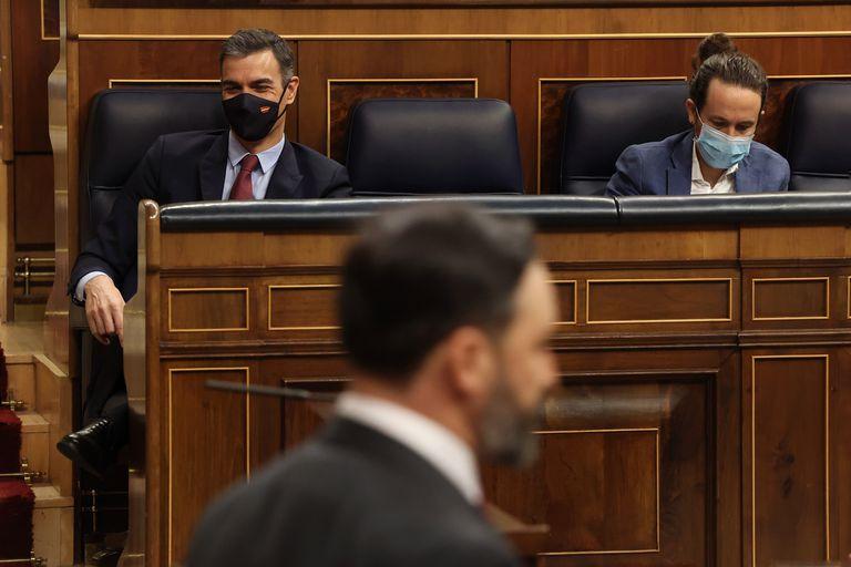 El presidente del Gobierno, Pedro Sánchez (izquierda); y el vicepresidente segundo del Gobierno, Pablo Iglesias (derecha), durante la intervención del líder de Vox, Santiago Abascal, en el pleno en el que se debate la moción de censura en el Congreso de los Diputados.