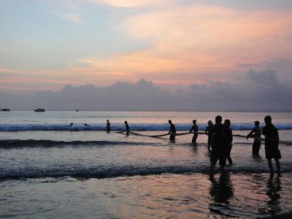 Un grupo de pescadores recoge sus redes al atardecer en la playa de Pangandaran (Indonesia).