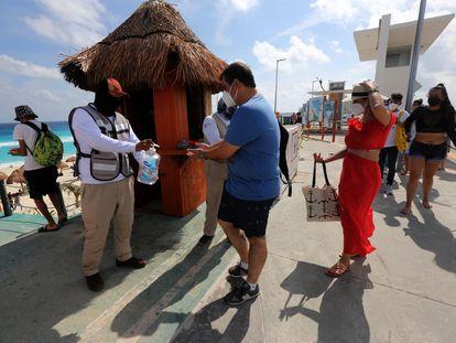 Un hombre reparte líquido desinfectante a turistas en la playa en Cancún, en enero.