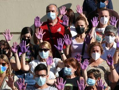 Personas con las manos moradas guardan un minuto de silencio en el Ayuntamiento de Málaga tras un asesinato machista el pasado 16 de julio.