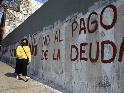 """Una mujer pasa delante de una pared pintada con la leyenda """"No al pago de la deuda"""", el 3 de agosto pasado en Buenos Aires."""