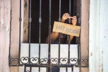 Una mujer ofreciendo comida en una casa de La Habana