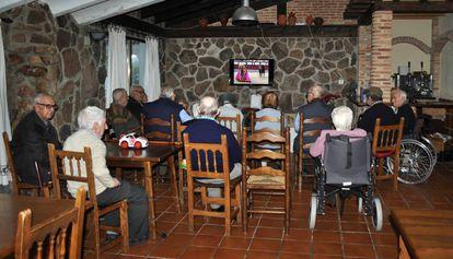 Un grupo de ancianos ven la televisión en una residencia