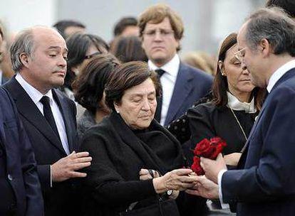 La viuda de Leopoldo Calvo-Sotelo recibe una rosa de su hijo Leopoldo.