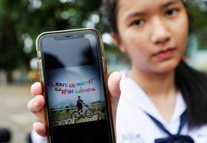 Una estudiante muestra una foto de su compañero Prachak Sutham, uno de los menores encerrados en la cueva de Tham Luang (Tailandia) el pasado lunes.