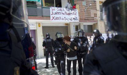 Mossos d'Esquadra detienen a una de las personas que intentaban evitar el desahucio de una familia en el barrio del Clot, en Barcelona.