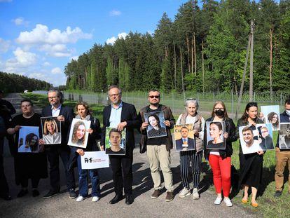 Miembros de Reporteros Sin Fronteras (RSF) y activistas posan ante la frontera lituana con Bielorrusia con fotos de periodistas bielorrusos detenidos por el Gobierno de Alexandr Lukashenko.