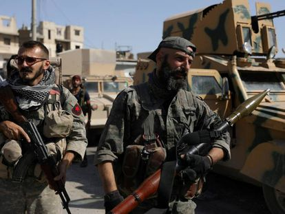 Combatientes de las Fuerzas Democráticas Sirias, junto a un vehículo militar en Raqa, en el norte de Siria, el pasado mes de octubre.