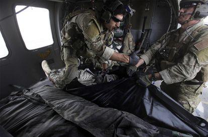 Dos militares estadounidenses depositan el cadáver de un soldado muerto en una bolsa para trasladarlo, el jueves en Kandahar.