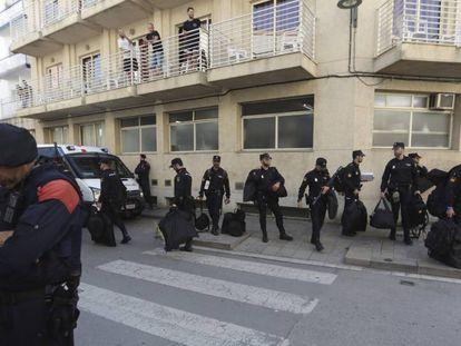 Un grupo de policías nacionales espera su transporte delante del hotel Mont-Palau de Pineda (Barcelona).