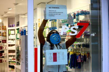 Una farmacéutica cuelga un cartel donde avisa que no le quedan mascarillas ni geles desinfectantes en Platja d'Aro (Girona).