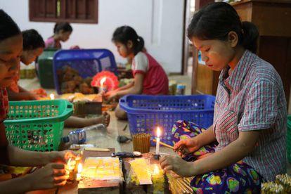 Niños elaborando cigarros en Myanmar.