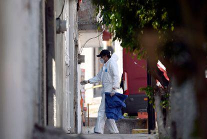 """Un trabajador forense ingresa a la casa del presunto asesino en serie Andrés """"N"""", quien fue detenido hace unos días, en el municipio de Atizapán de Zaragoza, Estado de México."""