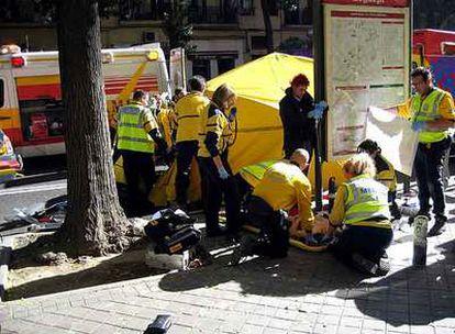 Los servicios de emergencias atienden en plena calle a uno de los heridos en la reyerta.