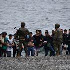 Soldados del Ejército de tierra junto a un grupo de migrantes en Ceuta, este martes.