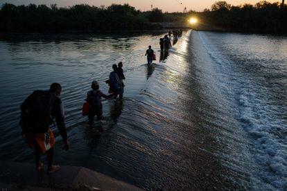 Un grupo de migrantes de Haití cruza el Río Grande para obtener alimentos y suministros cerca del puerto de entrada Del Rio-Akunya en Ciudad Akunya, Coahuila, México.