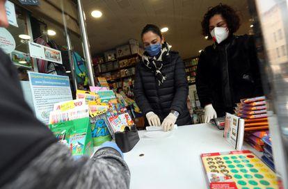 Las encargadas de una librería atienden a un cliente en Ponferrada el miércoles.