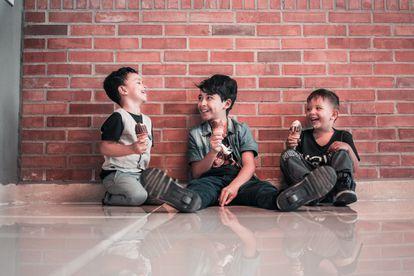 Tres niños se ríen, mientras comen un helado.