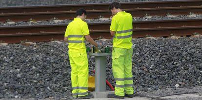 Trabajadores de ADIF revisan una baliza al costado de las vías (archivo).