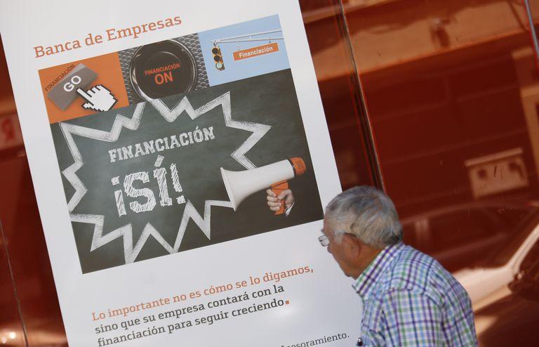 Sucursal bancaria con un cartel de financiación a empresas en una calle de Madrid.