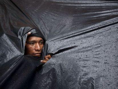 Un indígena Mbyá Guaraní se protege de la lluvia.