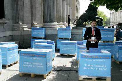Rajoy, rodeado de los cuatro millones de firmas, en cajas dispuestas en palés.