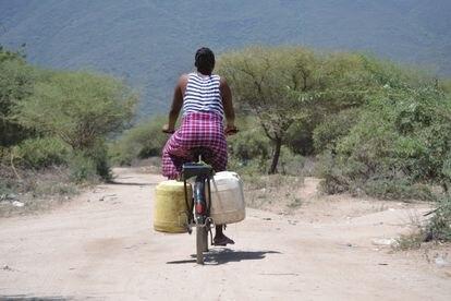 Sipha, una joven de 21 años, pedalea por los caminos de Msitu Wa Tembo cargada con varias garrafas de agua.