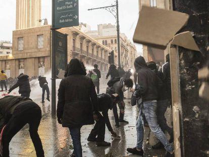 Un grupo de manifestantes se enfrenta a las fuerzas de seguridad libanesas, el sábado en Beirut.