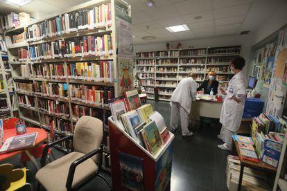 Carmen Guzmán, responsable de la biblioteca para pacientes del hospital Clínico, atiende a dos usuarias.