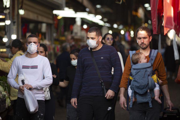 Un grupo de vecinos de Tel Aviv, algunos con mascarillas, pasean por las calles de la ciudad israelí.