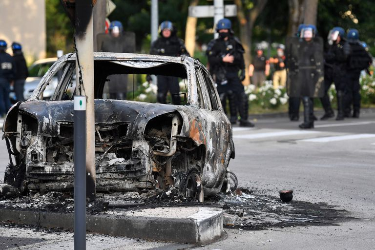 Gendarmes junto a un coche incendiado en el barrio Gresilles de Dijon, centro de los disturbios del fin de semana.