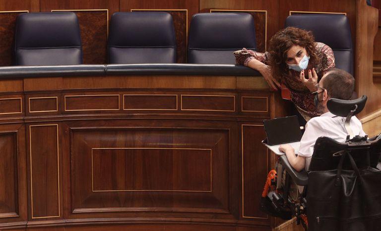 El portavoz de Podemos, Pablo Echenique, habla en el Congreso con la ministra de Hacienda, María Jesús Montero.