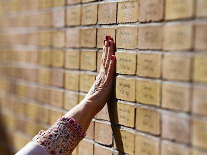 Una mujer toca el memorial del Holocausto durante su inauguración este domingo en Ámsterdam (Holanda).